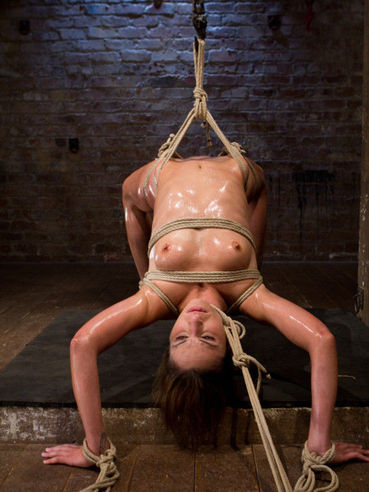 Brunette Amber Rayne is hanging tied up while her whole slim body is covered in dirt and cum.