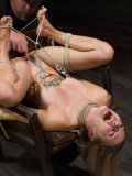 Missy Minks tied with ropes and getting spanked after her body is stretched in bondage.