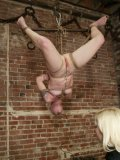 Poor Lorelei Lee is flipped around and upside down while she is suspended during hardcore bondage.