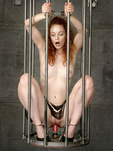 Handcuffed redhead girl Justine Joli toys her neat shaved pussy behind the bars