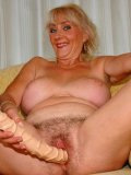 Blue-eyed blonde granny Ludmilla spreads her hairy pussy lips before taking dildo and cock