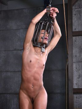 Nikki Darling makes out with a bald hottie before she is put into a cage during kinky bondage.