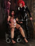 Latex clad redhead mistress Soma Snakeoil ties naked Leah Parker to wheelchair