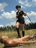 Strict domina Cindy Rella in black uniform punishes nude obedient soldier in the open air