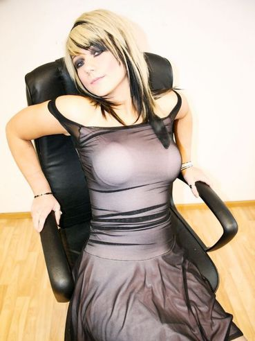 Flirtatious alternative lady Harriet in black nylons and dress poses in the empty room