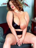 Playful chubby model Maria Moore dressed in red and black demonstrates her big knockers