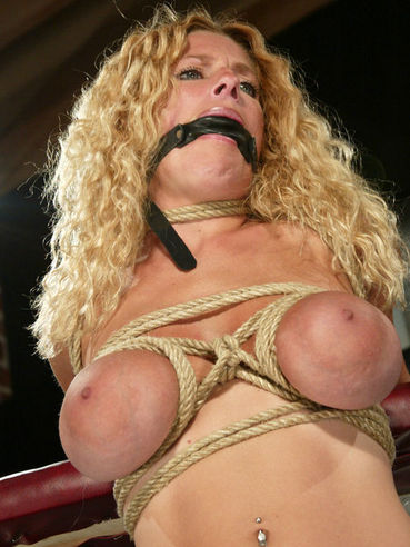 Curly haired blonde Goldie Star with DD boobs gets tied up and dildo fucked in a bar