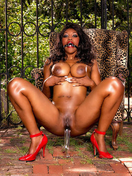 Busty black slave lady Nyomi Banxxx takes dildo after losing her red outfit