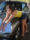 Shoeless girl Ryan Keely in sexy short denim skirt washes her car outdoors