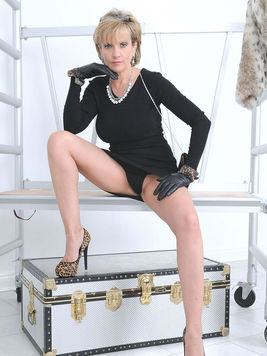 Elegantly dressed blonde Lady Sonia poses in front of a mirror for foot and legs fetish lovers.