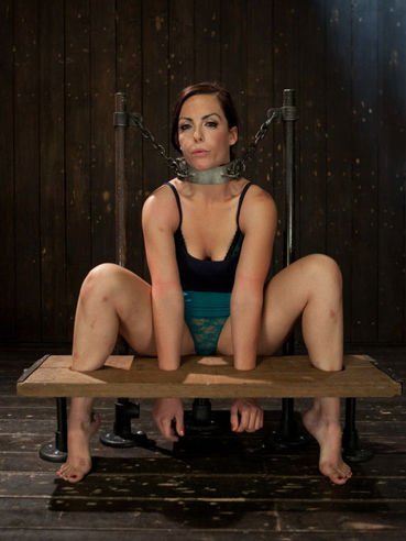 Hot redhead Bryn Blayne has her feet and arms secured to the pillory and she can't move at all.