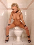 Naked blonde Liliane Tiger with shaved tattooed pussy pissing in the toilet bowl