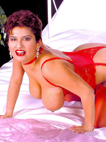 Chubby woman Helena dressed in red does some modeling and pulls out her heavy tits