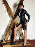 Fetish Lady Sonia dressed in leather, equipped with a whip waiting for her victim while posing.