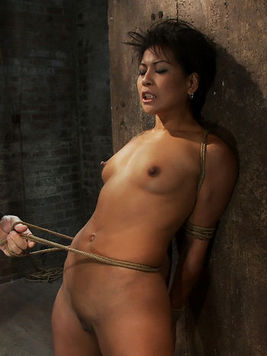 Exotic tight chick Max Mikita with hands behind her back stands still in the dungeon