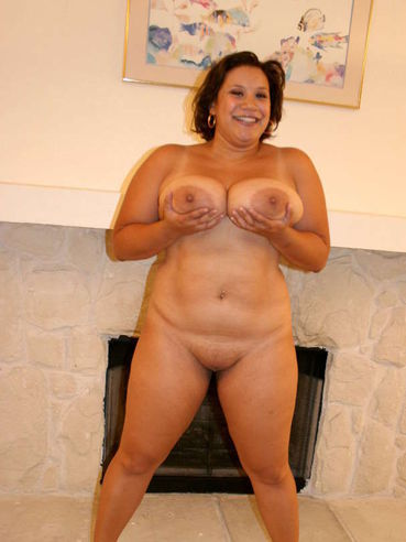 Fat woman Monet Staxxx with huge tits and fat hairless pussy removes her lingerie by the fireplace