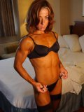 Muscle woman Jodi Leigh in black underwear pulls down her bra hesitatingly