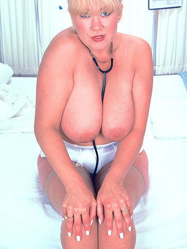 Chunky middle aged nurse Ginger dressed in white displays her big breasts