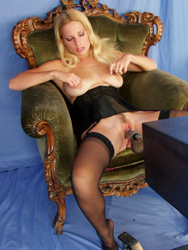 Blonde Goldie Star in black stockings and corset plays with vibrator as violator fucks her pussy