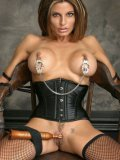 Slave babe Priscilla Russo in black corset and stockings shows off her round boobs and neat snatch