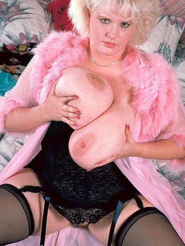 Fat blonde Roberta Smallwood in stockings and lingerie plays with her unbelievably big jugs