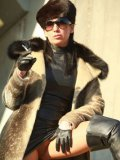 Stella Van Gent in fur coat, leather dress and high boots smokes a cigarette outdoors