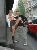 Blonde Angie in nylons, boots and mini skirt shows her bald pussy in the street