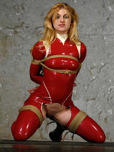 Tied up slave blonde Tawni Ryden in red latex suit gets her bald pussy banged by Steven St. Croix