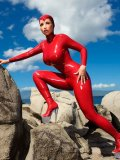 Bianca Beauchamp in skin tight red suit made of latex poses on a rocky beach