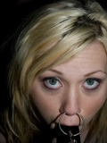 Slave blonde Samantha Sin with metal ring in her nose and dildo in her mouth gets her arms turned