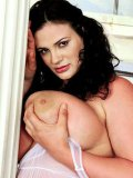 Fat brunette Miranda with nice massive tits takes off her white see-through negligee