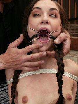 Sasha Grey hogtied, upside down and experiencing hardcore bondage before stimulated with water.