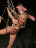 Slender slave blonde Kylie Wild gets tied, suspended and tormented in the dark of bdsm dungeon