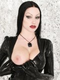 Latex beauty in black Vampirabat with raven hair and red lipstick flashes her boobs