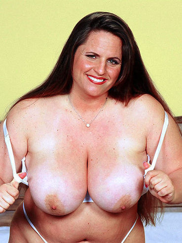 Long haired chunky brunette Gina Marie La Montana with gaint tits strips down to her white lingerie