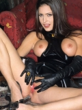 Smiling brunette Jessica Jaymes in long latex dress shows her shaved snatch and round tits.