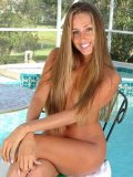 Completely naked long haired chick Lori Anderson plays with her long arm hair by the pool