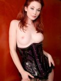 Flirty redhead in corset Justine Joli shows off her totally smooth pussy and pink nipples