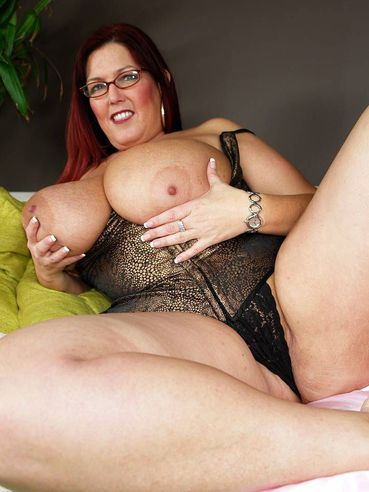 Giggling spectacled redhead mom Peaches Larue exposes her humongous tits before cocksucking