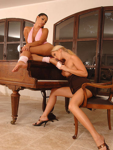 Fetish babe Sandra Shine and dreamy Zafira naked and licking feet and slits on top of a piano.