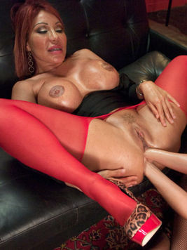 Ava Devine fisting and stretching out a red haired babes shaved hole during lesbo sex.