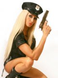 Blonde doll Saffron Taylor poses in sexy police woman uniform with gun in hands