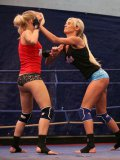 Two uniformed blondes Laura Crystal and Michelle Moist fight in the ring aggressively