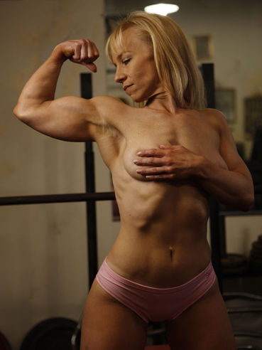 Long haired blonde bodybuilder Genie in pink bikini works out at the gym