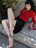 Brunette Mary Jane in black skirt and red blouse exposes her feet outdoors