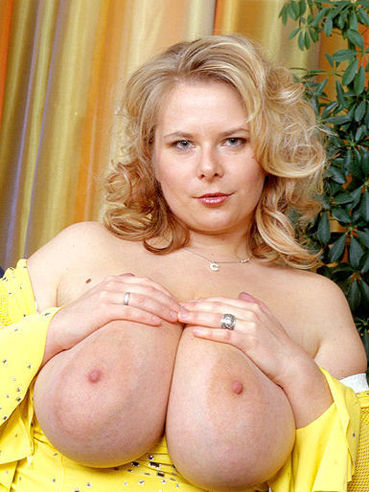 Fat german blonde Christiane in yellow blouse bares her big melons in the office