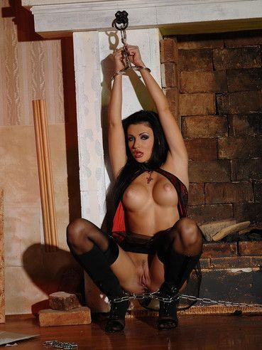 Handcuffed brunette Aletta Ocean displays her round tits, bald pussy and firm ass by the fireplace