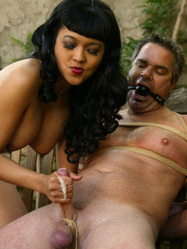 Asian Mika Tan plays with cock of her slave Frank Stone before drilling his bare ass with dildo
