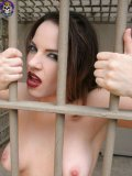 Completely naked crazy brunette Dana DeArmond with sexy body behind the bars