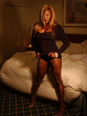 Ebony bodybuilder Tatianna Butler in black dress shows off her legs and cleavage in the bedroom